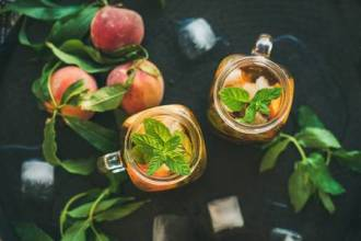 80696208-summer-refreshing-cold-peach-ice-tea-with-fresh-mint-in-glass-jars-on-metal-tray-background-top-view