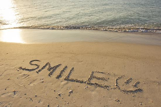 the-word-smile-written-in-the-sand-on-a-beach_u-l-pu6ubs0